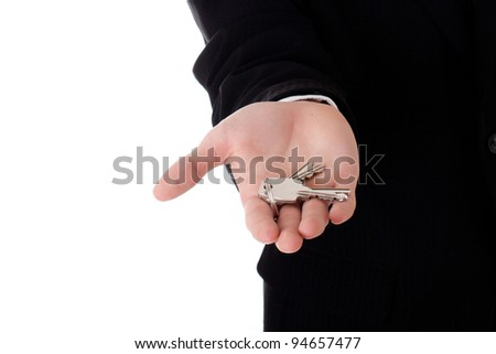 Man real estate agent offering keys studio isolated on white background - stock photo