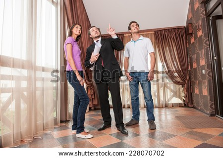 man real estate agent pointing to ceiling of new house. male agent holding plan of apartment and looking up - stock photo
