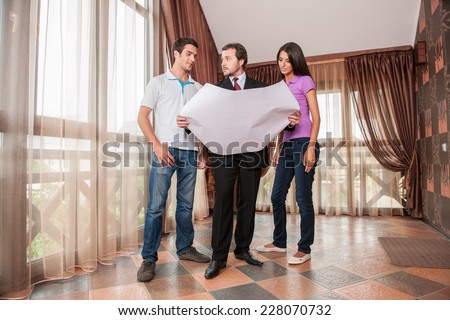 man real estate agent showing plan and layout of new house. male agent holding plan for clients couple - stock photo
