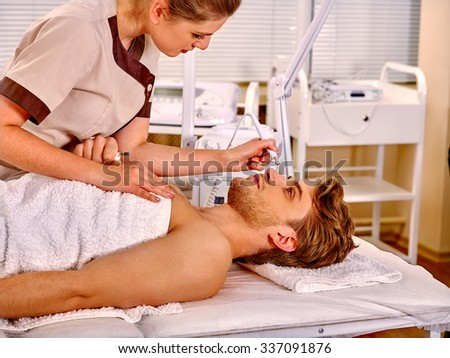 Man receiving electric facial hydradermie at beauty salon.  - stock photo