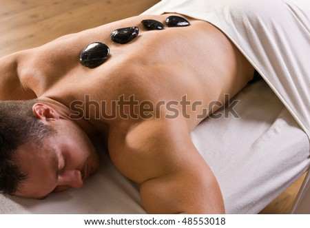 Man receiving hot stone therapy massage - stock photo