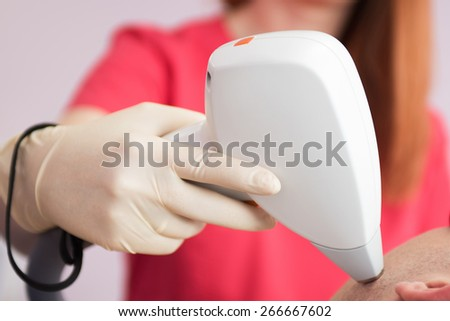 man receiving laser epilation at armpit on beauty center - stock photo