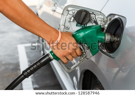 Man refilling the car with fuel on a filling station - stock photo