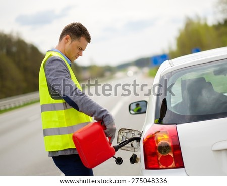 Man refuelling her car on a highway roadside  - stock photo