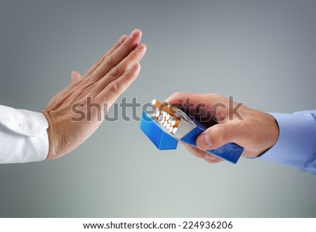 Man refusing a cigarette from a pack of smokes concept for quitting smoking and healthy lifestyle - stock photo