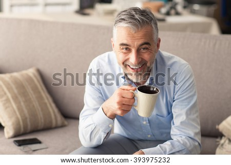 Man relaxing at home on the couch and having a coffee break, he is smiling at camera and holding a cup - stock photo