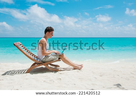 Man relaxing at the beach with laptop. Maldives island, ocean view