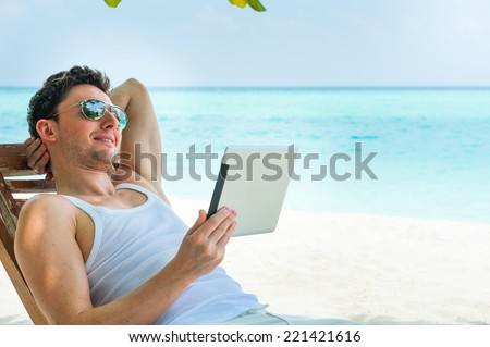 Man relaxing at the beach with tablet, laptop. Maldives island, ocean view - stock photo