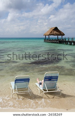 Man relaxing in a deck chair on the beach with a footbridge in the background - stock photo