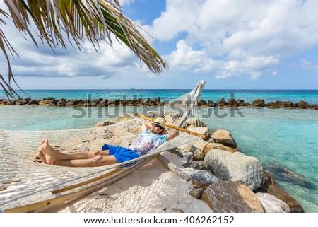 Man relaxing in a hammock - stock photo