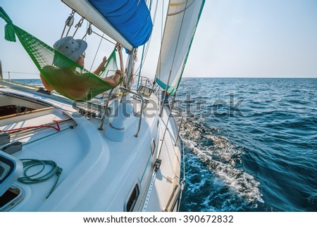Man relaxing in a hammock on the sailing boat in the sea