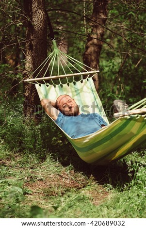 Man relaxing in hammock. Young caucasian man with beard swinging and resting in a hammock in a pleasant laziness of a summer outdoor weekend. Outdoor, adventures and nature vacation.  - stock photo