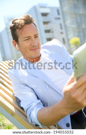 Man relaxing in resitential area with tablet