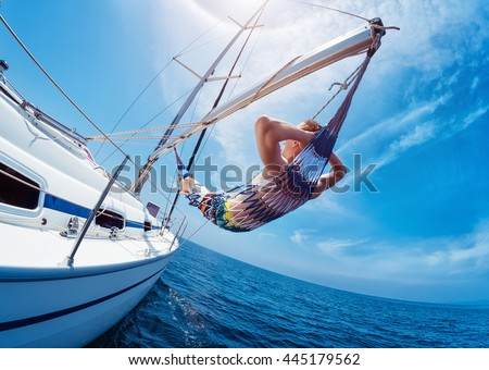 Man relaxing in the hammock set on the sail boat while sailing in the open sea - stock photo