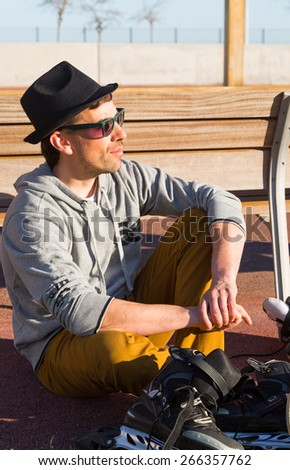 Man relaxing in the sun after a day of skating - stock photo