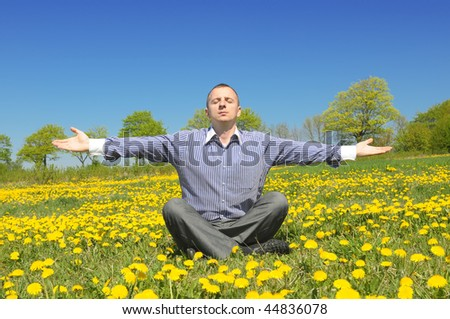 Man relaxing in yoga position between yellow flowers on the meadow. - stock photo