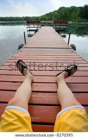 Man relaxing on a dock by small lake - stock photo