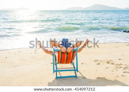 Man relaxing on beach, ocean view, Maldives island - stock photo