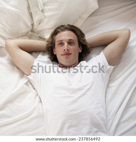 Man Relaxing on Bed - stock photo