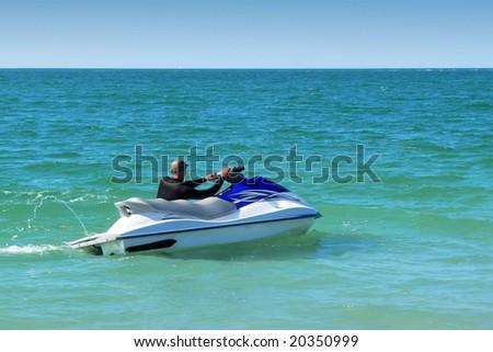 Man relaxing on idling jet ski - stock photo