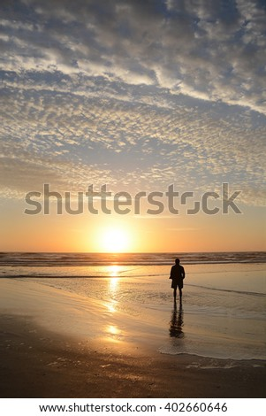 Man relaxing on the beach at sunrise, beautiful cloudy sky reflected on the beach, Jacksonville, Florida, USA.  - stock photo