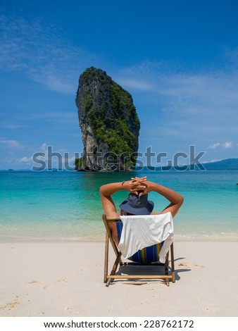 Man relaxing on the beach in Thailand - stock photo