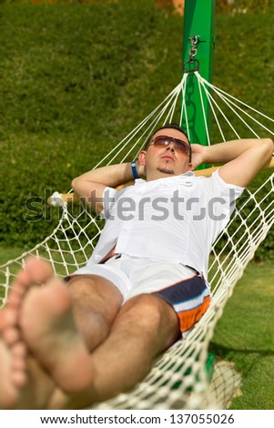 Man relaxing on the hammock - stock photo