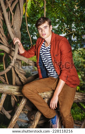 Man Relaxing Outside. Wearing a dark reddish brown jacket, unbuttoned, striped under shit, brown corduroy pants, a young handsome guy is sitting on a wooden fence with rattan trees, looking at you.  - stock photo