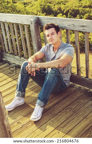 Man Relaxing Outside. Wearing a gray T shirt, jeans, white sneakers, a young handsome guy is sitting on the wooden floor, back against fence in a remote location, relaxing.  - stock photo