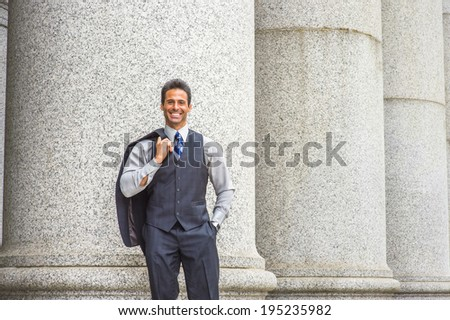 Man Relaxing Outside. Wearing a light gray shirt, dark blue vest, necktie, jacket taken off on shoulder, a  handsome, middle age businessman is standing by columns outside,  smiling, looking at you.  - stock photo