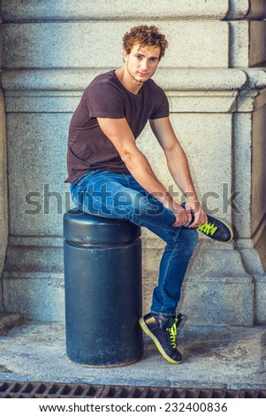 Man Relaxing Outside. Wearing dark brown T shirt, blue jeans, black sneakers, a young sexy guy with curly hair is sitting on a metal stake on the corner, crossing leg, looking at you. - stock photo