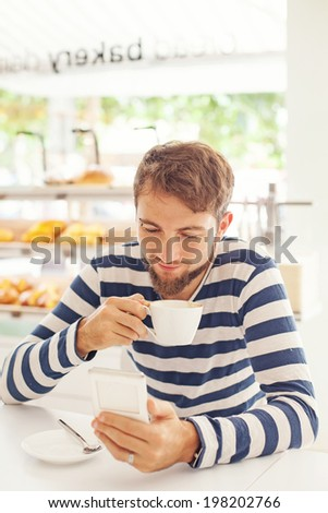 Man relaxing, reading news in the morning from his mobile phone and drinking coffee - stock photo