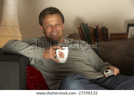 Man Relaxing With Coffee And Television - stock photo