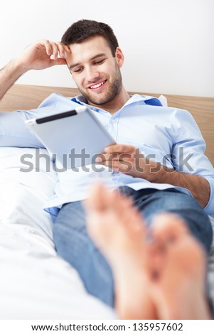 Man relaxing with digital tablet - stock photo