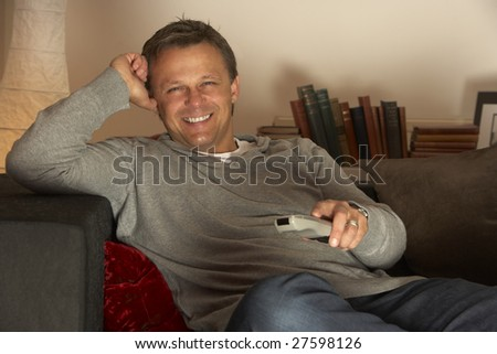 Man Relaxing With Remote Control - stock photo