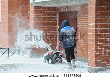 man removes snow in the yard of a multistory building with snow machines - stock photo