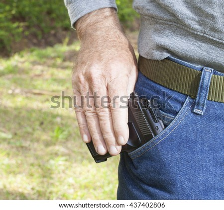 Man removing a handgun from his front pants pocket