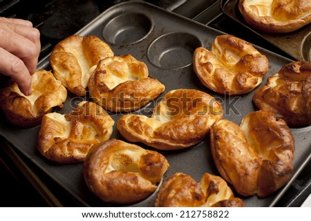 Man removing freshly baked individual fluffy golden Yorkshire puddings from a baking tray - stock photo