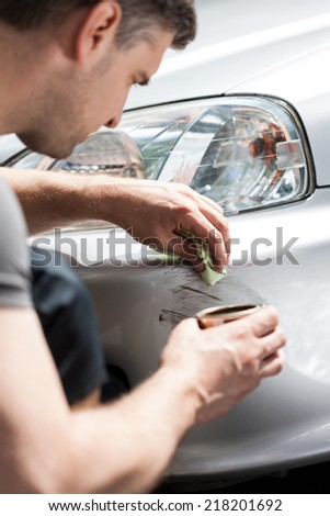 Man removing scratches from car bumper, vertical - stock photo
