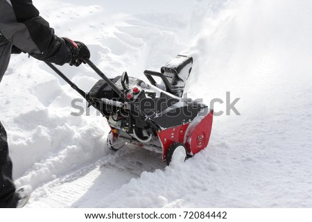 Man removing snow after storm with a snow-blower - stock photo