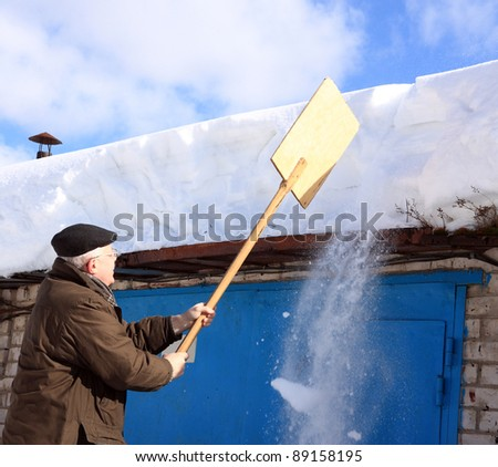 Man removing snow from a roof with a shovel; manual snow removal - stock photo