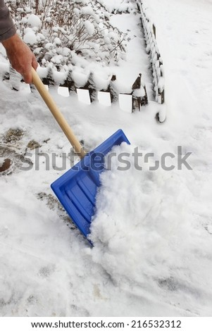 Man removing snow from the sidewalk after snowstorm - stock photo