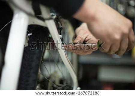 man repairing a bike in his workshop - stock photo