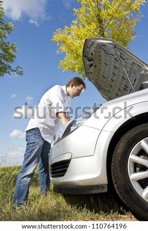 Man repairing a broken car - stock photo