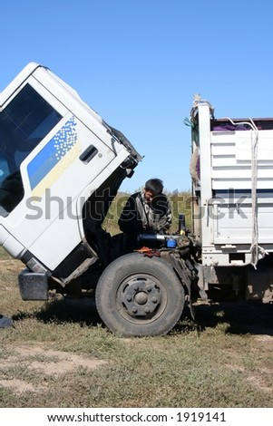 Man repairing a broken truck - stock photo