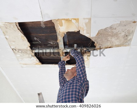 Man repairing collapsed ceiling. Ceiling panels damaged  huge hole in roof from rainwater leakage.Water damaged ceiling . - stock photo