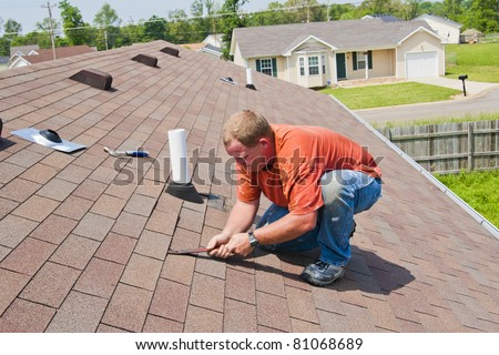 Man repairing damage to shingles after strong storm came through and water was coming down into home - stock photo