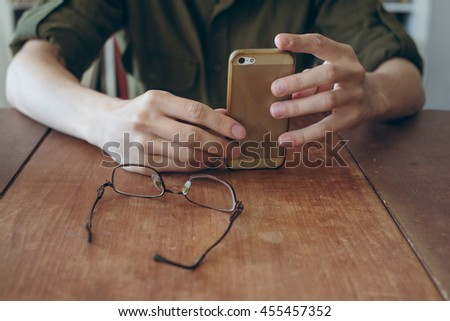 man rest with smartphone , glasses on the table