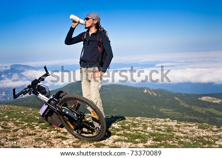 Man resting after cycling ascent - stock photo