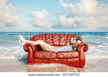 man resting in leather couch on the beach - stock photo